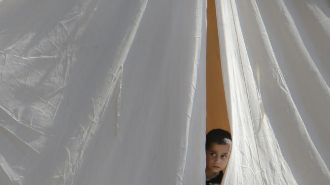 FILE - A Syrian refugee boy peers from a tent in a camp in Boynuyogun, Turkey, Tuesday, June 14, 2011. (AP Photo/Vadim Ghirda, File)