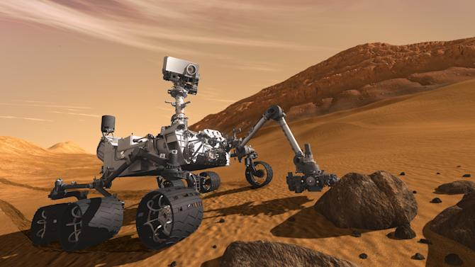 FILE - In this 2011 artist's rendering provided by NASA/JPL-Caltech, the Mars Science Laboratory Curiosity rover examines a rock on Mars with a set of tools at the end of its arm, which extends about 2 meters (7 feet). The mobile robot is designed to investigate Mars' past or present ability to sustain microbial life. Curiosity is set to land in a crater near the Martian equator in August 2012 to begin a two-year mission. (AP Photo/NASA/JPL-Caltech,File)