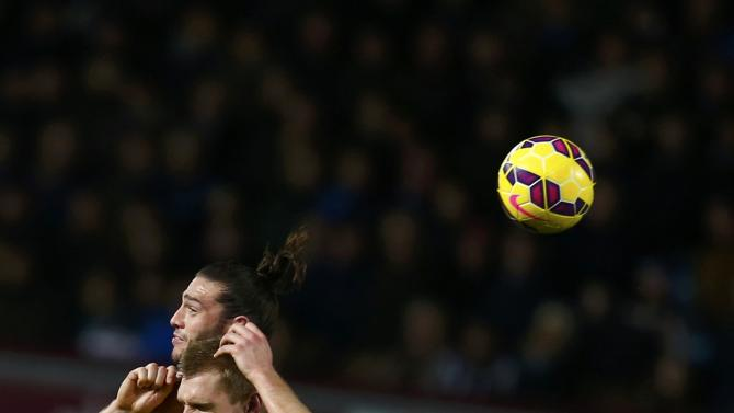 West Ham United's Andy Carroll challenges Arsenal's Per Mertesacker during their English Premier League soccer match at Upton Park in London