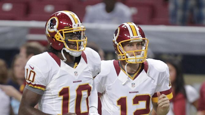 FILE - In this Sept. 16, 2012, file phot, Washington Redskins quarterbacks Robert Griffin III (10) and Kirk Cousins (12) warm up before the start of an NFL football game against the St. Louis Rams in St. Louis. A rookie will start at quarterback for the Redskins on Sunday. It will be either Griffin or Cousins facing the Cleveland Browns.  (AP Photo/Tom Gannam, File)