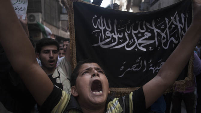 "FILE - In this Friday, Sept. 21, 2012 file photo, a Syrian boy shouts slogans against the regime in front of a flag of the armed Islamic opposition group, the Nusra front, during a demonstration in the Bustan al-Qasr neighborhood of Aleppo, Syria. Al-Qaida's branch in Iraq claimed responsibility on Monday for the killing last week of 48 Syrian soldiers and nine Iraqi guards in western Anbar province . Arabic, background, from the Quran reads, ""There is not God but Allah, and Muhammad is his messenger."" (AP Photo/ Manu Brabo, File)"