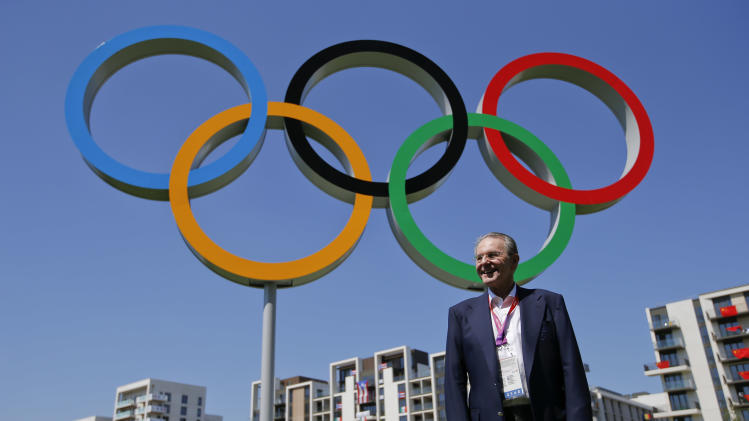 IOC President Jacques Rogge poses in front of the Olympic rings during his visit to the Athletes' Village at the Olympic Park, Monday, July 23, 2012, in London. (AP Photo/Jae C. Hong)