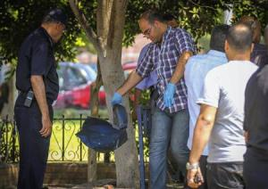 Egyptian security officials inspect a site hit by a bomb attack targeting a traffic security post near a court house in Cairo's Heliopolis district