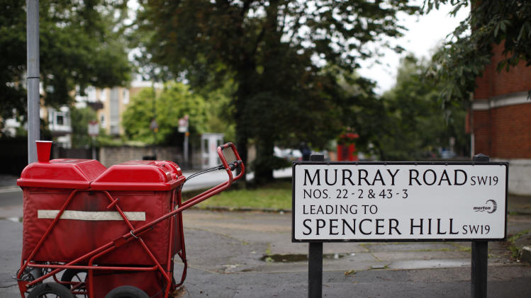 A Royal Mail caddy is parked next to a road sign in Wimbledon village, England, Sunday, July 8, 2012. Andy Murray of Britain will face Roger Federer of Switzerland in a men's singles final match at the All England Lawn Tennis Championships on Sunday afternoon. (AP Photo/Anja Niedringhaus)
