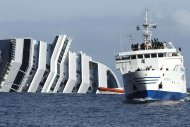 A ferry boat, right, sails past the grounded cruise ship Costa Concordia off the Tuscan island of Giglio, Italy, Sunday, Jan. 22, 2012. Rescuers on Sunday resumed searching the above-water section of the capsized Costa Concordia cruise liner, but choppy seas kept divers from exploring the submerged part, where officials have said there could be bodies. Civil protection officials said that until the waves slack off, divers would not swim into the submerged part of the vessel just off the port of Giglio, a tiny Island off the Tuscan coast. (AP Photo/Pier Paolo Cito)