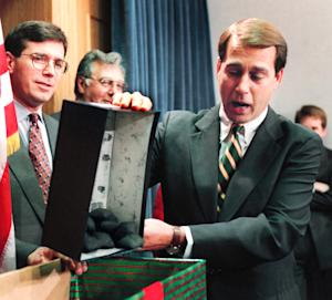 FILE - In this Dec. 21, 1995, file photo Rep. John Boehner, R-Ohio, dumps out coal, his so-called Christmas gift to President Clinton, during a news conference about the federal budget on Capitol Hill as Congressional Republicans tried to restart balanced budget talks on day six of the partial government shutdown. President Barack Obama and his officials are doing their best to drum up public concern over the shock wave of spending cuts that could strike the government in just days. So it's a good time to be alert for sky-is-falling hype. (AP Photo/Denis Paquin, File)