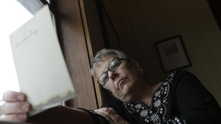 """In this Tuesday, Feb. 12, 2013 photo, Sister Carol Gray looks at a photograph of her father at her home in Tuscaloosa, Ala. In October 2012, Carol learned about the """"perversion files"""" kept by the Boy Scouts from local news accounts. She told her brother Jim. Neither had heard of the Scouts' documents previously. To Jim, they held few surprises, save that the Scouts suspected something was wrong with their father and did enough to protect Scouts, but no one else. (AP Photo/Dave Martin)"""