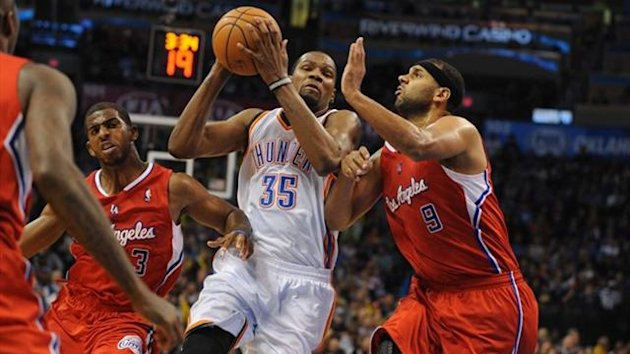 Oklahoma City Thunder small forward Kevin Durant (35) handles the ball while being guarded by Los Angeles Clippers small forward Jared Dudley (9) and Clippers point guard Chris Paul (3) (Reuters)
