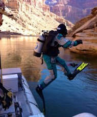 USGS hydrologist Tom Sabol enters the Colorado River in scuba diving gear to sample sediment in preparation for the November flood from the Glen Canyon Dam.