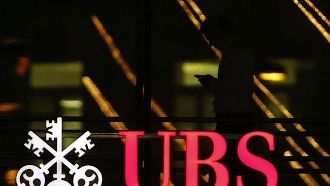 Employee uses a mobile phone as he walks past the logo of Swiss bank UBS in Zurich