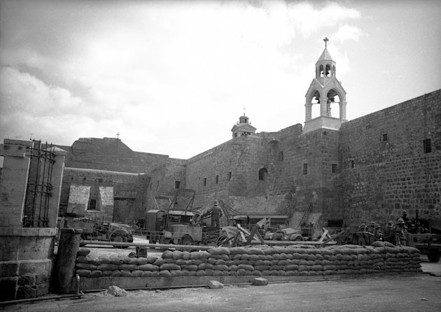 FILE - This circa 1947 file photo shows the Church of the Nativity in Bethlehem, Palestine, occupied by British soldiers and mechanized units and fortified with sandbags and trucks. The Palestinians on Wednesday, June 27, 2012 made a final push to have UNESCO recognize the Church of the Nativity in Bethlehem in the Israeli-controlled West Bank as an endangered World Heritage site, despite misgivings by Christian denominations and a cool response from the U.N. agency. (AP Photo/James Mills)