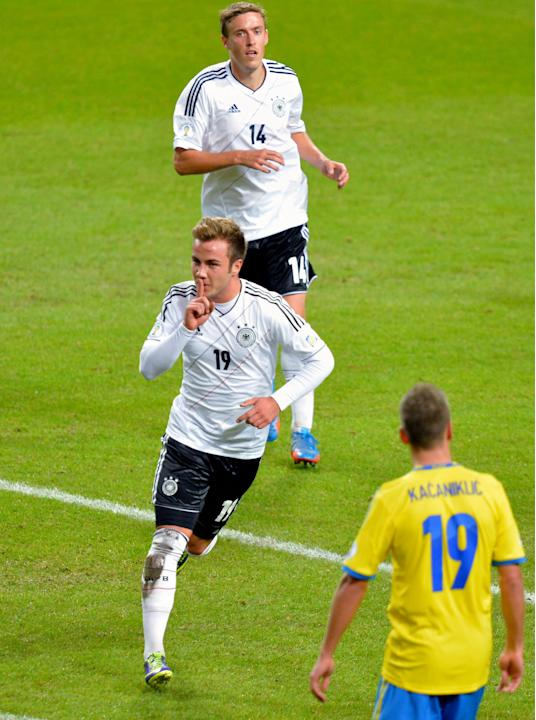 Germany's Mario Goetze, centre, celebrates his equalizing goal to take the score to 2-2, with team mate Max Kruse, behind, during the 2014 World Cup group C qualifying soccer match between Sweden and