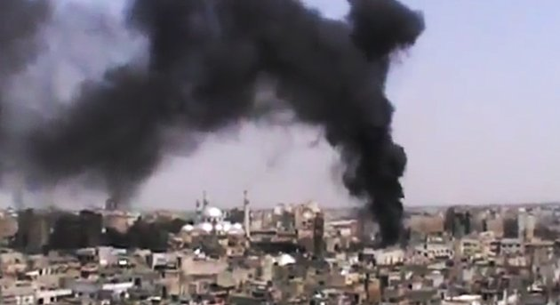 This image made from amateur video released by the Shaam News Network and accessed Monday, June 18, 2012, purports to show black rising from buildings in Homs, Syria. Syrian forces renewed shelling of the central city of Homs on Monday, one day after the head of the U.N. observers' mission demanded that warring parties allow the evacuation of women, children, elderly and sick people, activists said. (AP Photo/Shaam News Network via AP video) TV OUT, THE ASSOCIATED PRESS CANNOT INDEPENDENTLY VERIFY THE CONTENT, DATE, LOCATION OR AUTHENTICITY OF THIS MATERIAL