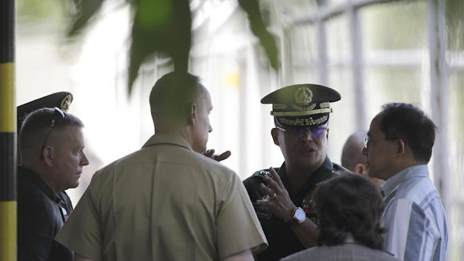 """Philippine Armed Forces Chief Gen. Gregorio Pio Catapang, second from right facing camera, discusses with Eduardo Oban Jr., right, the Director on the Presidential Commission on the Visiting Forces Agreement and other U.S. military officers after U.S. soldier PFC Joseph Scott Pemberton, a suspect in the killing of Filipino transgender Jeffrey """"Jennifer"""" Laude, was flown in to his detention Wednesday, Oct. 22, 2014 at Camp Aguinaldo, the headquarters of the Philippine armed forces at suburban Quezon city, northeast of Manila, Philippines.  Catapang announces Wednesday the U.S. military turned over the suspect in the gruesome killing of a transgender Filipino to the Philippine military's main camp in the capital Wednesday, easing a looming irritant over his custody, officials said.(AP Photo/Bullit Marquez)"""
