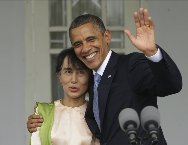 U.S. President Barack Obama, right, waves as he embraces Myanmar democracy activist Aung San Suu Kyi after addressing members of the media at Suu Kyi's residence in Yangon, Myanmar, Monday, Nov. 19, 2