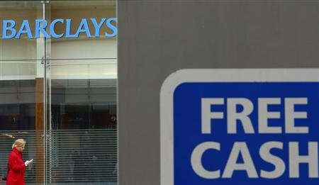 A woman walks past a Barclays Bank in Leicester