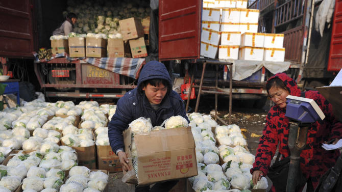 A Chinese man carries a box of cauliflowers at a farm produce wholesale market in Fuyang in central China's Anhui province Friday Jan. 11, 2013. China's inflation spiked to a six-month high in December after a freezing winter pushed up vegetable prices, possibly complicating efforts to sustain a shaky economic recovery, the National Bureau of Statistics reported Friday. (AP Photo) CHINA OUT