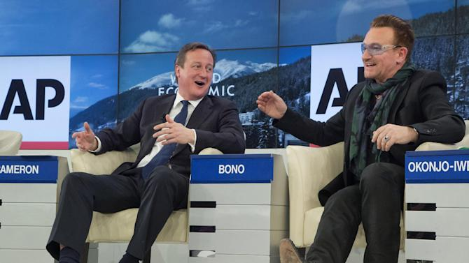 """British Prime Minister David Cameron, left, and rock star Bono speak during the panel discussion """"The Post-2015 Goals: Inspiring a New Generation to Act"""", the fifth annual Associated Press debate, at the World Economic Forum in Davos, Switzerland, Friday, Jan. 24, 2014. (AP Photo/Michel Euler)"""