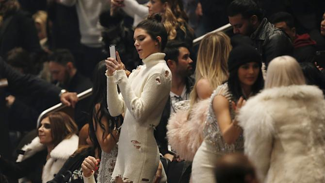 Kendall Jenner uses her cellular device during Kanye West's Yeezy Season 3 Collection presentation and listening party during New York Fashion Week