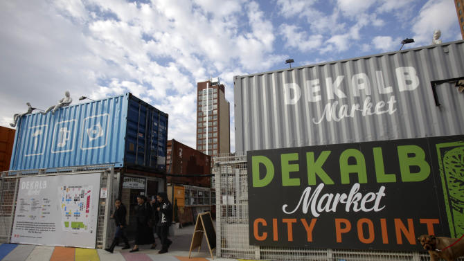In this Nov. 20, 2011 photo, pedestrians walk through the Dekalb Market in the Brooklyn borough of New York. The outdoor market, created out of salvaged shipping containers, is one of a number of stalled construction sites in New York City that are being converted into creative spaces. (AP Photo/Seth Wenig)