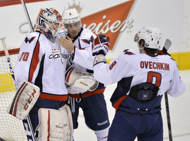 Capitals' Ribeiro and Ovechkin congratulate goaltender Holtby after his shutout against the Winnipeg Jets during their NHL hockey game in Winnipeg