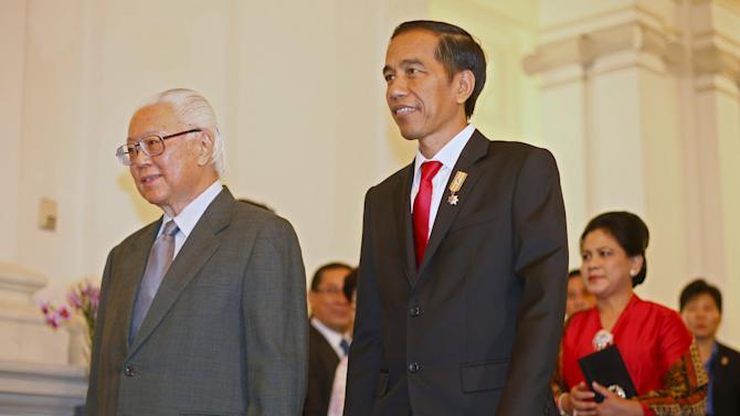 Indonesian President Joko Widodo walks with Singaporean counterpart Tony Tan to a meeting at the Istana in Singapore