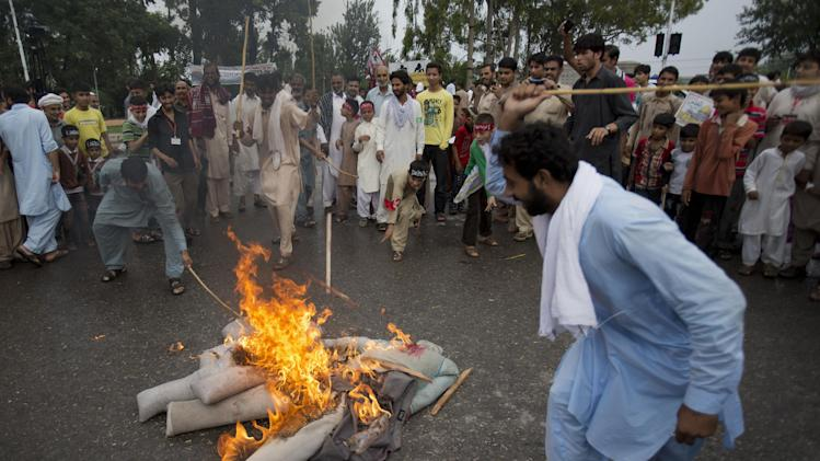 Pakistani protesters burn effigies of Israeli leaders during a pro-Palestinian rally marking Al-Quds (Jerusalem) Day in Islamabad, Pakistan, Friday, July. 25, 2014. Al-Quds Day is the last Friday of the Muslim holy month of Ramadan declared by the Iranian late spiritual leader Ayatollah Ruhollah Khomeini as an international day of struggle against Israel and for the liberation of Jerusalem. (AP Photo/B.K. Bangash)