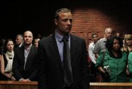 &quot;Blade Runner&quot; Oscar Pistorius awaits the start of court proceedings in the Pretoria Magistrates court February 19, 2013. Pistorius, a double amputee who became one of the biggest names in world athletics, was applying for bail after being charged in court with shooting dead his girlfriend, 30-year-old model Reeva Steenkamp, in his Pretoria house. REUTERS/Siphiwe Sibeko