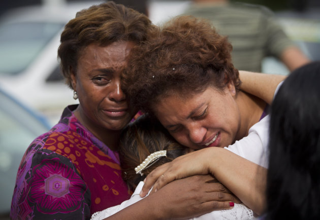 Relatives of a family killed by a mudslide hug outside a church during a wake for victims in Jamapara, Rio de Janeiro state, Brazil, Tuesday Jan. 10, 2012. Sergio Carvalho, his wife Solange and their son Tiago were buried by a mudslide that killed at least eight people. (AP Photo/Victor R. Caivano)