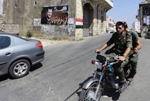 Syrian soldiers ride a motorcycle past a posterof President …