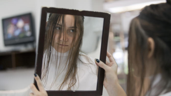 In this Feb. 5, 2013 photo, a customer looks at her reflection as she gets her haircut at a beauty salon in Sao Paulo, Brazil. L'Oreal's tests have revealed that half of all Brazilian women smell their own hair at least once a day. The dedication to texture and scent also makes Brazil a prime testing ground for new products, said Blaise Didillon, head of research and innovation for L'Oreal Brazil. (AP Photo/Andre Penner)