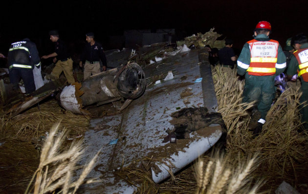 Pakistani rescue workers and police officers look for survivors amid the wreckage of a passenger plane which crashed on the outskirts of Islamabad, Pakistan, Friday, April 20, 2012. A Pakistani passen