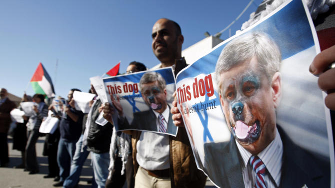 "Palestinians hold pictures of Canadian Prime Minister Stephen Harper superimposed with a face of a dog during a protest following his  remarks about the Palestinian UN bid for an observer state status, in front of Canadian representative offices in the West bank city of Ramallah, Wednesday, Nov. 28, 2012. Harper has threatened ""there will be consequences"" if Palestinian Authority President Mahmoud Abbas does not end his campaign for the Palestinian Authority to be recognized by the UN as a non-member observer state. (AP Photo/Majdi Mohammed)"