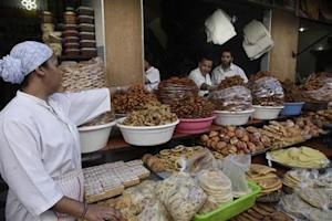 A vendor sells traditional cakes of fried honey and flour pastries to customers ahead of Ramadan in Rabat