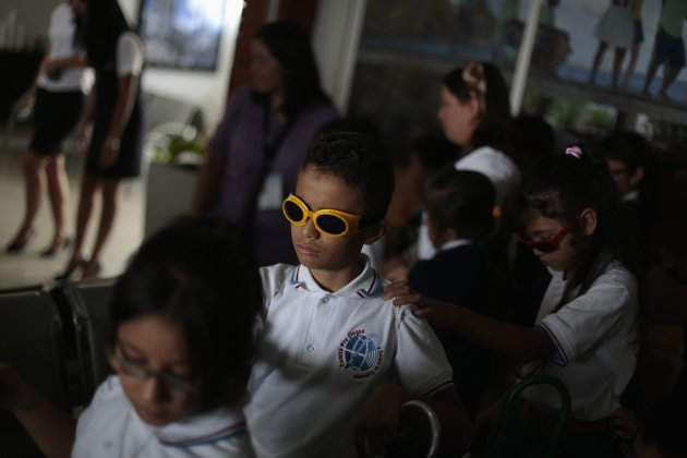 Visually impaired children enter the waiting room of an airline before boarding a plane in the international airport of La Aurora in Guatemala City