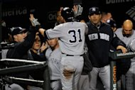 Ichiro Suzuki of the New York Yankees is congratulated in the dugout by teammates and manager Joe Girardi (R) after Suzuki scored on a 2-run double hit by Robinson Cano in the top of the ninth inning against the Baltimore Orioles during Game One of the American League Division Series at Oriole Park at Camden Yards, in Baltimore, Maryland. The Yankees won 7-2