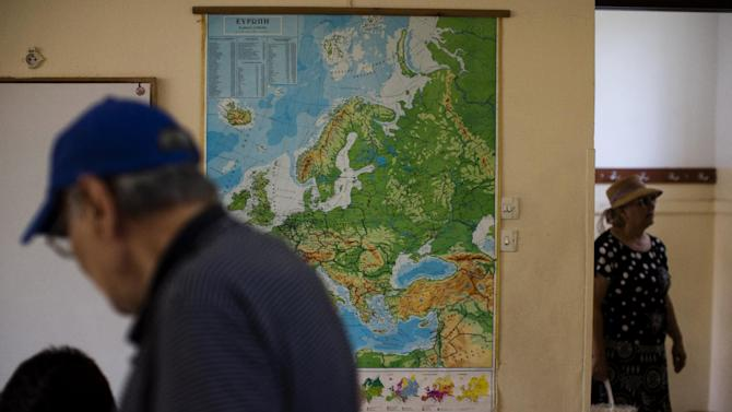 A map of Europe is on display in a polling station as people arrive to cast their vote in Athens, Sunday, July 5, 2015. Greeks were voting Sunday in a critical bailout referendum, with opinion polls showing people evenly split on whether to accept creditors' proposals for more austerity in exchange for rescue loans, or defiantly reject the deal. (AP Photo/Emilio Morenatti)