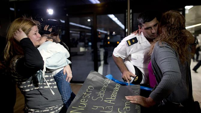 A crew member of Argentine ship Libertad, second right, kisses a relative as he arrives in Buenos Aires airport, Argentina, Thursday, Oct. 25, 2012.  Nearly 300 navy cadets arrived to Argentina's capital from Ghana on an Air France charter hired by the government after Argentina's President Cristina Fernandez refused to negotiate the release of the Argentine naval sailing ship, Libertad. The ship had been held in a port outside Ghana's capital Oct. 2, when a Ghana court ruled to detain the vessel as collateral for Argentina's unpaid debts. (AP Photo/Natacha Pisarenko)