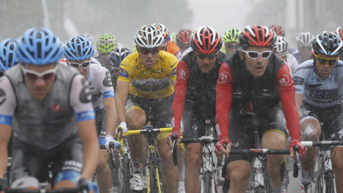 The pack with three-time Tour de France winner Alberto Contador of Spain, far right, and Thor Hushovd of Norway, wearing the overall leader's yellow jersey, center, rides in pouring rain during he sixth stage of the Tour de France cycling race over 226.5 kilometers (140.7 miles) starting in Dinan, Brittany, and finishing in Lisieux, Normandy, western France, Thursday July 7, 2011. (AP Photo/Christophe Ena)