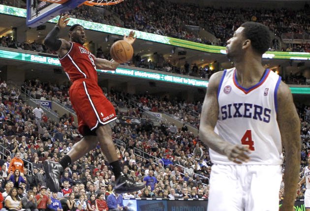 Heat forward James dunks the ball near the 76ers forward Wright during their NBA basketball game in Philadelphia