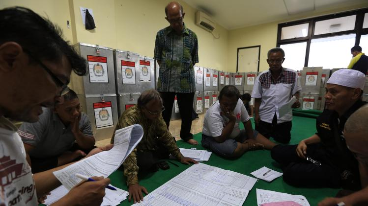Election commission official Saidi reads a document stating the number of votes collected in ballot boxes, at Bendungan Hilir in Jakarta