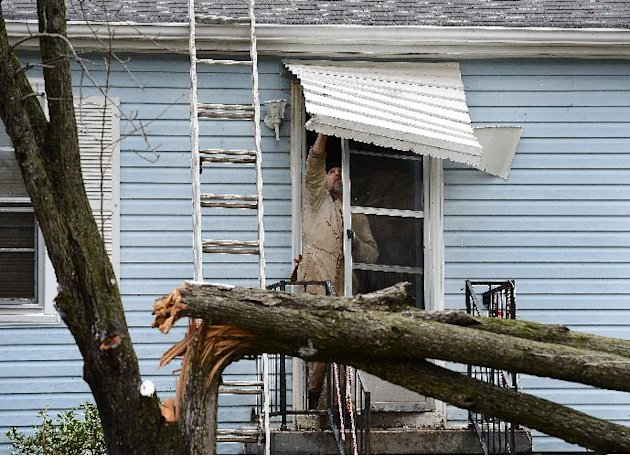 Harold Grant tries to repair his front door awning before cutting up a tree that broke in his front yard  after a tornado touched down, damaging 25 homes and knocking out power Wednesday, Jan. 30, 201