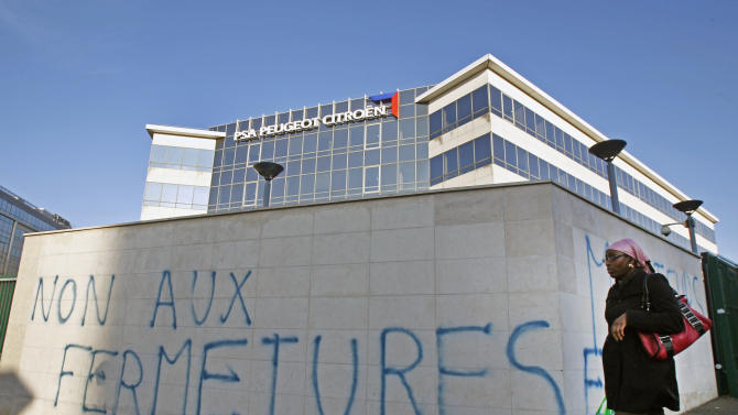 "FILE - In this Dec. 11, 2012 file photo, a woman walks past the entrance of a Peugeot Citroen unit, with graffiti reading, ""No to closures"", following a demonstration in which the office was partially vandalized, Poissy, west of Paris. With its long vacations, short hours and myriad workers' rights, France has a reputation for being a hard place to do business. Now add this to the mix: A law working its way through parliament would grant amnesty to workers who have ransacked their company's offices or threatened their bosses in the midst of labor disputes. (AP Photo/Remy de la Mauviniere, File)"