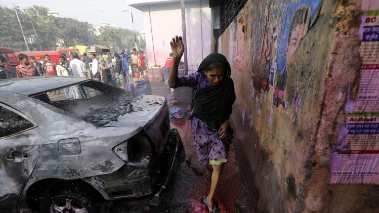 A woman steps on colored water thrown to control fire by a police van, after clashes between Bangladesh's Jamaat-e-Islami party activists and police, in Dhaka
