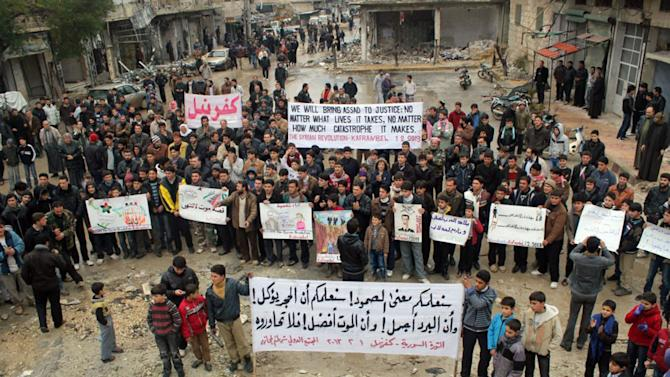 """This citizen journalism image provided by Edlib News Network, ENN, which has been authenticated based on its contents and other AP reporting, shows anti-Syrian regime protesters carrying banners during a demonstration, at Kafr Nabil town, in Idlib province, northern Syria, Friday, Feb. 1, 2013. The Arabic banner, foreground, reads: """"we will teach you the meaning of the steadfastness, we will teach that the stone is eaten, and the cold is beautiful, and the death is better, so don't dialogue with him (Bashar Assad)."""" (AP Photo/Edlib News Network ENN)"""