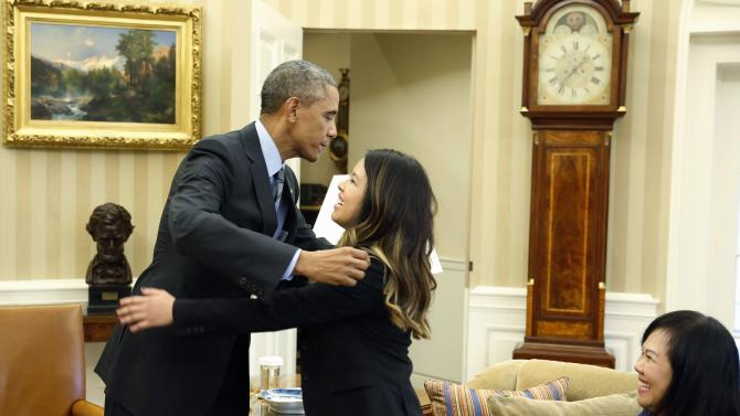 U.S. President Obama leans over to hug Dallas nurse Pham next to her mother Diana at in the Oval Office in Washington