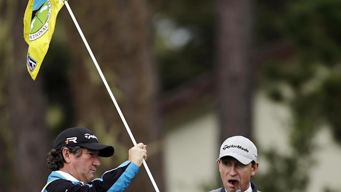 Hockey great Wayne Gretzky puffs on a cigar as he grabs the pin on the second green of the Monterey Peninsula Country Club Shore Course during the first round of the AT&T Pebble Beach Pro-Am golf tournament, Thursday, Feb. 7, 2013, in Pebble Beach, Calif. (AP Photo/Ben Margot)
