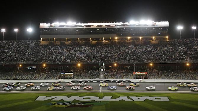 Martin Truex Jr., top left, and Carl Edwards, bottom left, lead the group of cars to start the second of two NASCAR Sprint Cup qualifying auto races at Daytona International Speedway in Daytona Beach, Fla., Thursday, Feb. 20, 2014