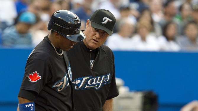 Toronto Blue Jays' Yunel Escobar, left, has his knee looked at by trainer Hap Hudson, right, and manager John Farrell during the third inning against the Seattle Mariners in a baseball game in Toronto on Tuesday, July 19, 2011. (AP Photo/The Canadian Press, Frank Gunn)