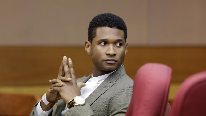R&B singer Usher waits for a child custody hearing to begin, Friday, Aug. 9, 2013, in Atlanta. A judge in Atlanta is set to hear arguments in the child custody battle between Usher and his ex-wife. Tameka Foster Raymond requested the hearing earlier this week after the former couple's son got caught in a pool drain while in the care of Usher's aunt. (AP Photo/David Goldman)